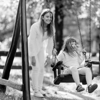 Handicapped child enjoying the swing outdoors with sister
