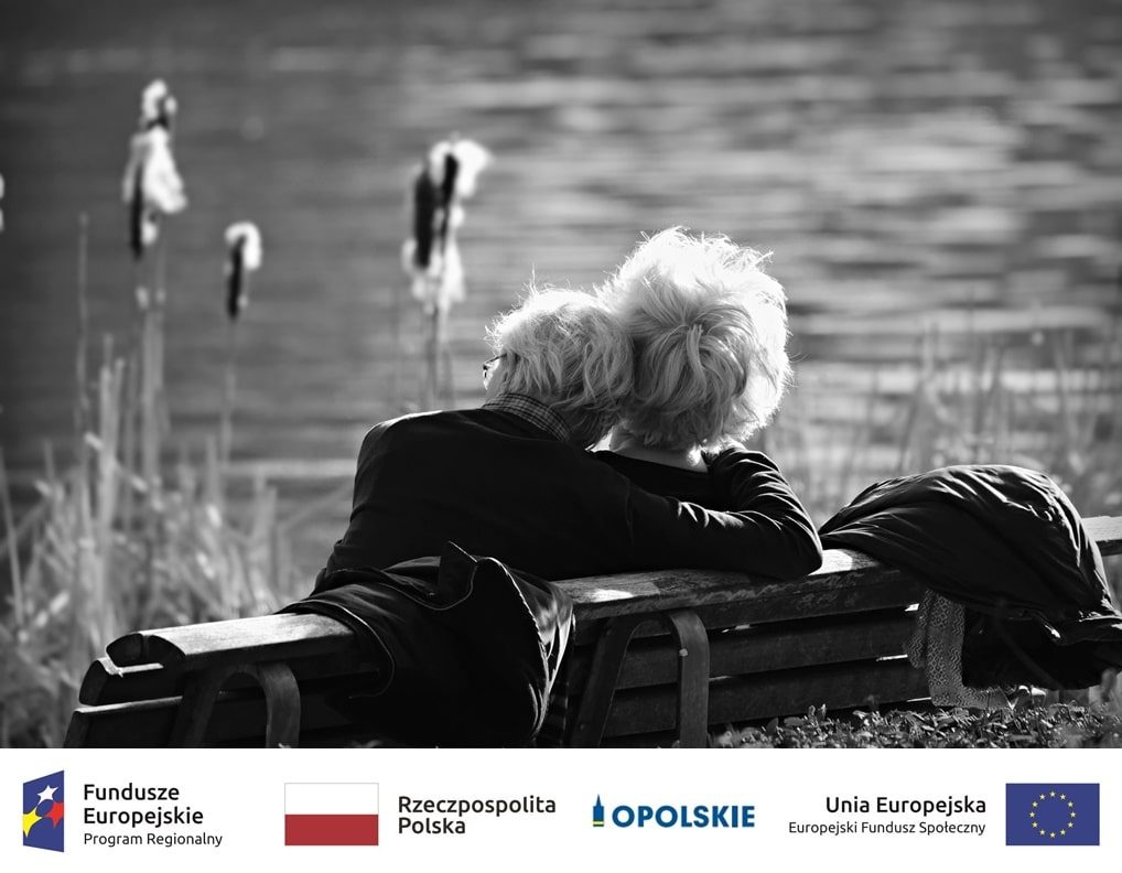 osoby starsze siedzą na ławce nad jeziorem